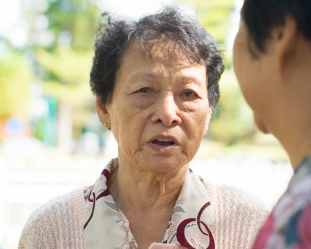 Sadness senior woman telling sad story to her friend, with tears in eyes, natural outdoor park. photo