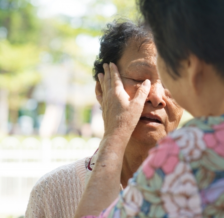 Candid shot of a mature woman consoling her tearful crying old mother at outdoor natural park.  photo