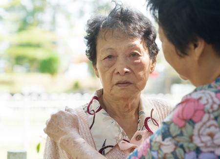 persona deprimida: Franco disparo de una mujer madura que consuela a su madre llorando de edad en el parque natural, al aire libre.