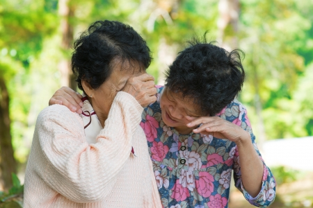 Sad senior Asian women  in grieving the loss of a loved one. Outdoor park. photo