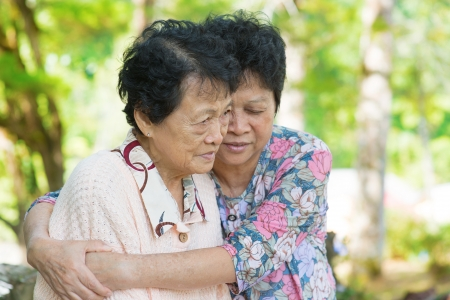 sad old woman: Candid shot of an Asian mature woman hugs and consoling her crying old mother at outdoor natural park.