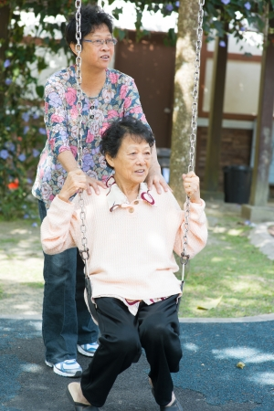 80s Asian old mother and 60s senior daughter playing swing at outdoor garden park. photo