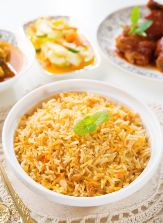 Biryani rice or briyani rice, curry chicken and salad, traditional indian food on dining table. Stock Photo - 21373984