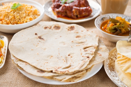 Chapatti roti, curry chicken, biryani rice, salad, masala milk tea and papadom. Indian food on dining table. photo