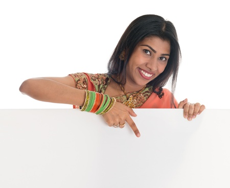 Traditional Indian woman in sari holding and pointing to blank billboard. Portrait of attractive young Asian female model isolated on white background.