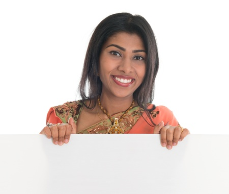 indian saree: Traditional Indian woman in sari holding a blank billboard. Portrait of attractive young Asian female model isolated on white background.