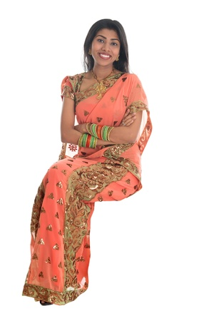 Full body traditional Indian woman in sari sitting on a transparent chair isolated over white background. photo