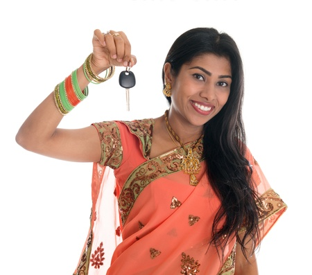 Attractive traditional Indian woman in sari holding her first own car key isolated on white background. Beautiful Asian woman model. photo