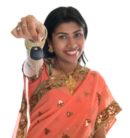 Attractive traditional Indian woman in sari holding her first own car key isolated on white background. Focus on car key.