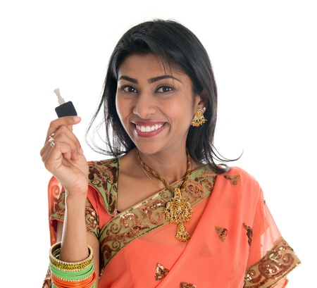 Estate agent. Happy Traditional Indian business woman or realtor showing keys. Isolated over white background. photo