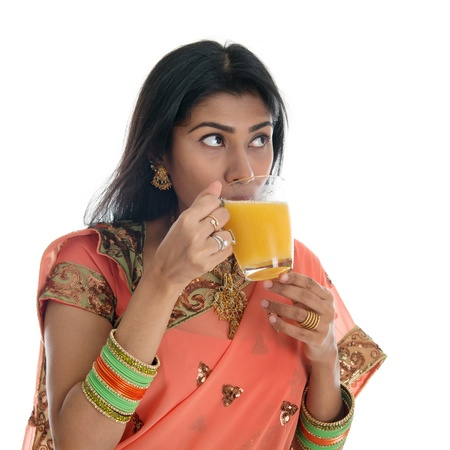Traditional Indian woman in sari drinking orange juice, isolated on white background. photo
