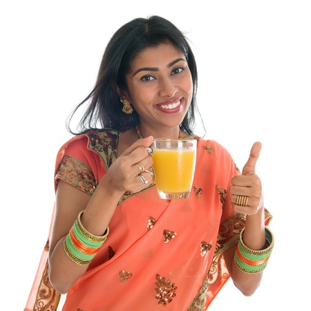 Happy traditional Indian woman in sari drinking a glass of orange juice showing thumb up, isolated on white background. photo