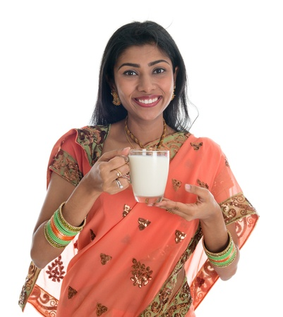 Traditional Indian woman in sari drinking milk, isolated on white background. photo