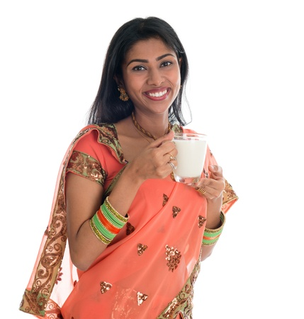 Happy Traditional Indian woman in sari drinking soy bean milk, isolated on white background. photo