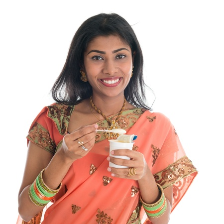 indian traditional: Happy Traditional Indian woman in sari eating yogurt, isolated on white background. Stock Photo