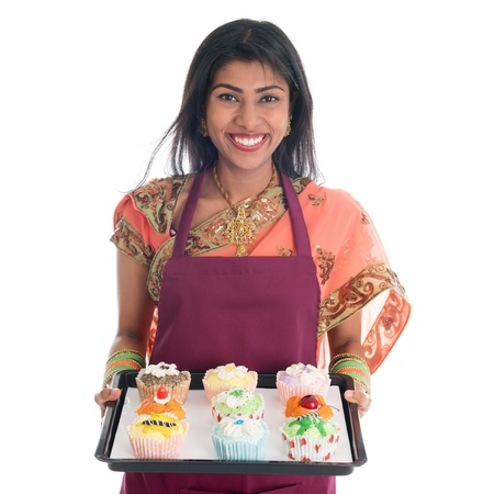 Traditional Indian woman in sari baking bread and cupcakes, wearing apron holding tray isolated on white. photo