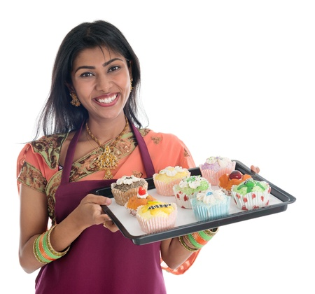 Happy Traditional Indian woman in sari baking bread and cupcakes, wearing apron holding tray isolated on white. photo