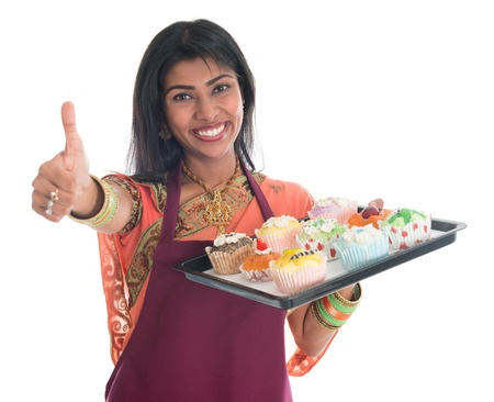 indian cooking: Happy Traditional Indian woman in sari baking bread and cupcakes and showing thumb up, wearing apron holding tray isolated on white. Stock Photo