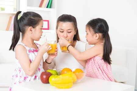sharing food: Asian family drinking orange juice. Happy Asian parent and children enjoying cup of fresh squeeze fruit juice at home.