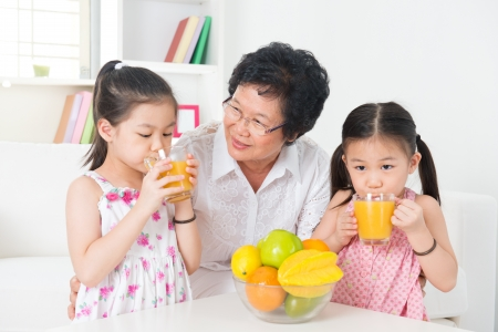 Asian family drinking orange juice. Happy Asian grandparent and grandchildren enjoying cup of fresh squeeze fruit juice at home. photo