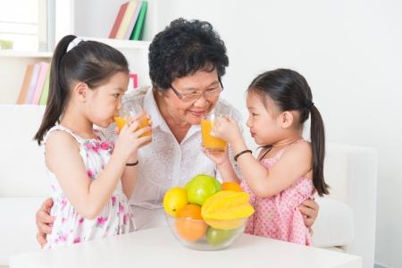 亞洲家庭飲用橙汁。亞洲快樂的祖父母和孫子在家中享受一杯鮮榨果汁。醫療保健的概念。 版權商用圖片