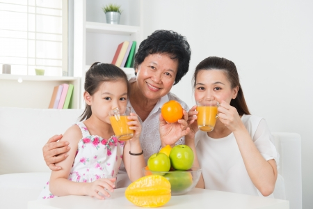 three generations: Asian family drinking orange juice. Happy Asian grandparent, parent and grandchild enjoying cup of fresh squeeze fruit juice at home.
