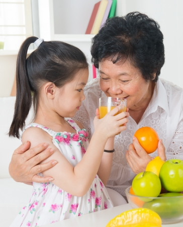 sharing food: Asian family drinking orange juice. Happy Asian grandchild sharing cup of fresh squeeze fruit juice with grandmother at home.