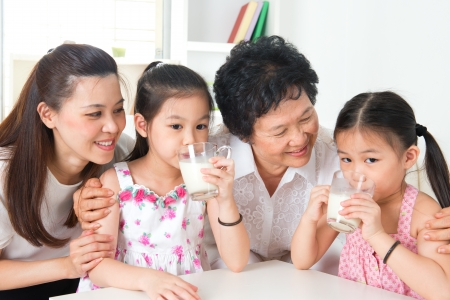 three generations: Drinking milk. Happy multi generations Asian family at home. Beautiful grandmother, mother  and granddaughters, healthcare concept.