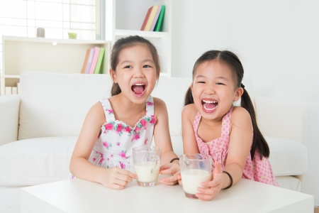 Children drinking milk. Asian family at home. Beautiful sister drinks milk together. photo