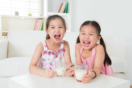 soja: Ni�os bebiendo leche. Familia asi�tica en casa. Bebidas hermana hermosa la leche. Foto de archivo