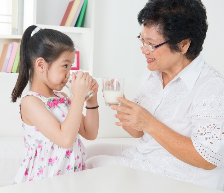 Drinking milk. Happy multi generations Asian family at home. Beautiful grandmother and granddaughter, healthcare concept. photo