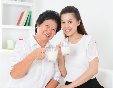 Consumptiemelk. Gelukkig Aziatische familie consumptiemelk thuis. Mooie senior moeder en volwassen dochter, gezondheidszorg concept. Stockfoto