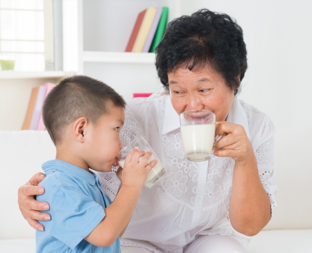 Drinking milk. Happy multi generations Asian family drinking milk at home. Beautiful grandmother and grandson, healthcare concept. photo
