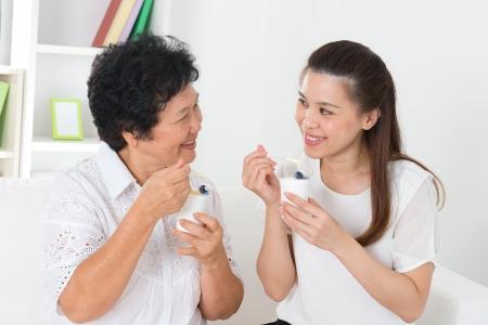 Het eten van yoghurt. Gelukkig Aziatische familie eet yoghurt thuis. Mooie senior moeder en volwassen dochter, gezondheidszorg concept.