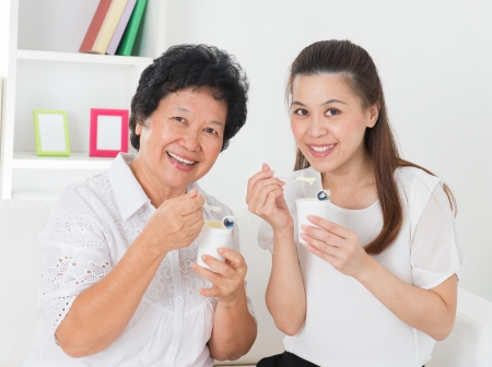 japanese dessert: Eating yogurt. Happy Asian family eating yoghurt at home. Beautiful senior mother and adult daughter, healthcare concept.