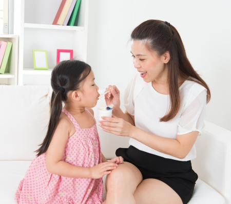 kids food: Eating yogurt. Happy Asian family eating yoghurt at home. Beautiful mother  feeding child, healthcare concept. Stock Photo
