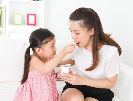 sharing food: Eating yogurt. Happy Asian family eating yoghurt at home. Beautiful child feeding mother, healthcare concept. Stock Photo