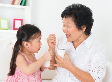 yogur: Comer yogur. Familia asiática feliz comer yogur en casa. Hermosa abuela y su nieto, el concepto de salud. Foto de archivo