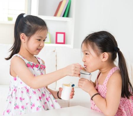 sharing food: Eating yogurt. Happy Asian children eating yoghurt at home. Beautiful sisters . Healthcare concept. Stock Photo