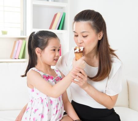Comer helado. Familia asiática feliz que come el helado en casa. Hermosa madre de alimentación infantil. Foto de archivo - 21412039