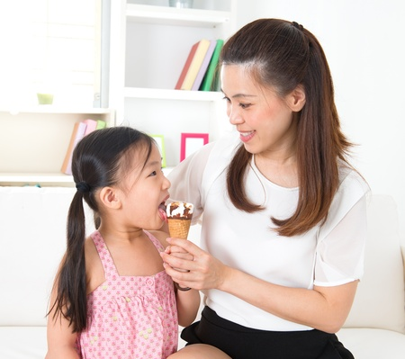 Eating ice-cream. Happy Asian family sharing ice-cream at home. Beautiful child licking ice-cream cone. photo