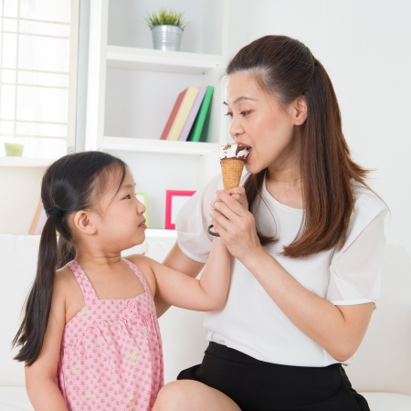 woman with ice cream: Eating ice-cream. Happy Asian family sharing ice-cream at home. Beautiful child feeding mother.
