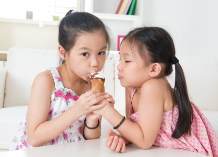 licking: Eating ice cream cone. Asian children sharing an ice cream at home.  Beautiful girls model.