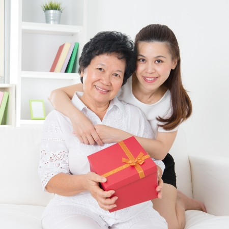 Senior woman receiving a gift from adult daughter, beautiful Asian family at home. Stock Photo