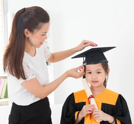 graduate hat: Asian child graduation, teacher adjusting cap for student indoor.