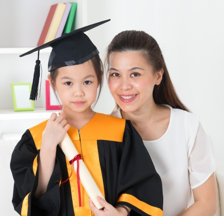 Asian school kid graduate in graduation gown and cap. Taking photo with mother. Stock Photo
