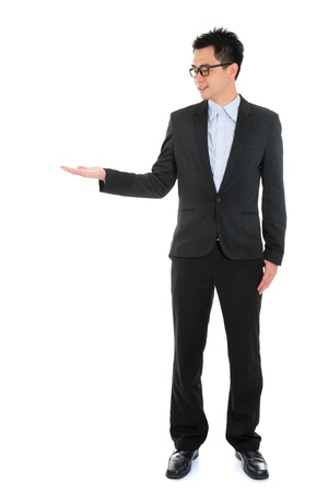 something: Full body portrait of young handsome smiling Asian business man hand showing blank empty space, standing isolated over white background
