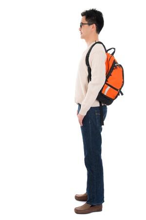 Vista lateral de cuerpo completo Asia estudiante adulto en ropa casual con mochila de pie aislado en fondo blanco. Modelo masculino asiático.