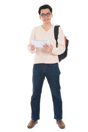 Full body Asian adult student in casual wear  using digital computer tablet pc standing isolated on white background. Asian male model. photo
