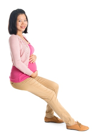 Full body six months pregnant Asian woman sitting on invisible chair, looking at camera,  isolated on white background. photo
